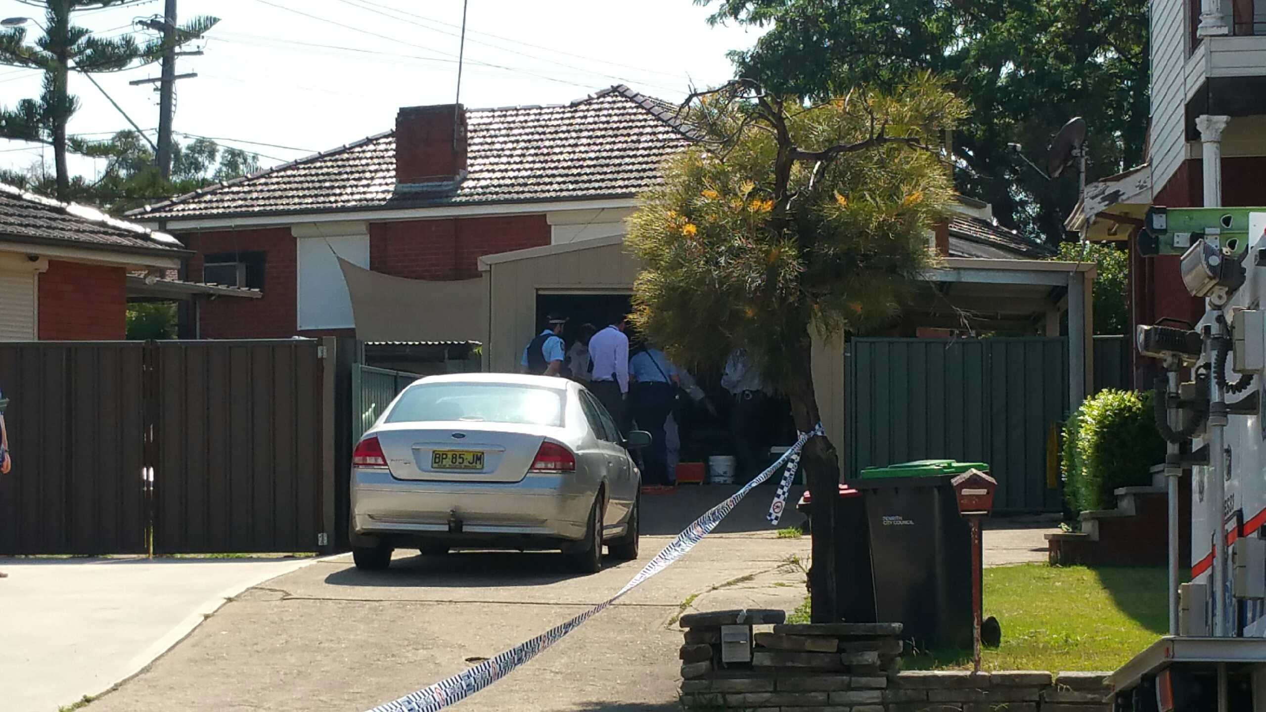 Police officers inspecting a garage. Photo: Emily Newton